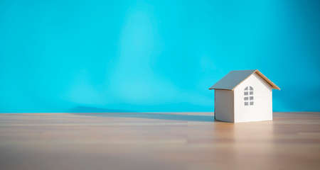 White paper house design isolated on blue background, shadows showing warmth