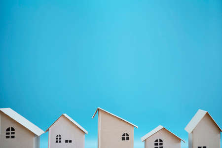 White paper house designs arranged separately on blue background. The empty space can include advertising text. 版權商用圖片