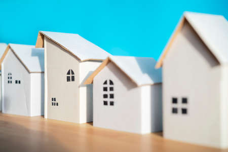 White paper house designs arranged separately on blue background, shadows showing warmth