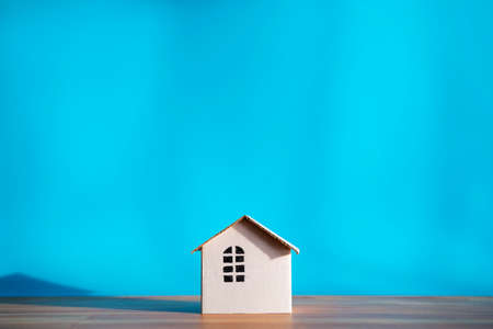White paper house design isolated on blue background, shadows showing warmth. The empty space can include advertising text.