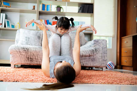 Beautiful young woman and charming little girl are smiling while doing yoga together in living room