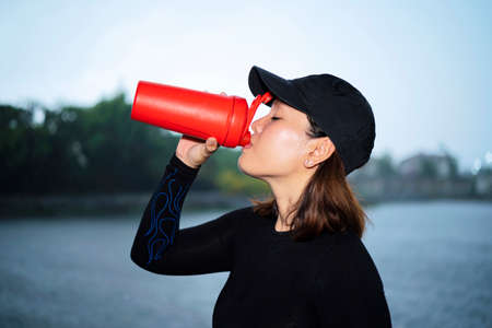 Fitness woman drinking water. woman athlete takes a break, she drinking water, out on a run on a hot day 版權商用圖片