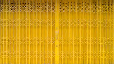 Old vintage iron yellow doors. Steel folding gates. Selective focus.