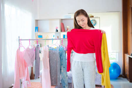 Women choose clothes to wear, clothing, fashion, style and people concept - happy woman choosing clothes at home