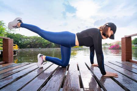 Healthy women doing planking exercises on pier during sport training 版權商用圖片