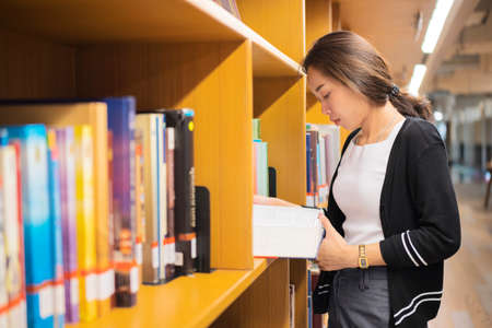 Asian woman reading a book in library. Portrait of college girl reading book in library