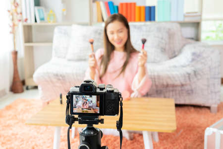 Young beautiful Asian woman professional beauty vlogger or blogger recording make up tutorial to share on social media. Young beauty blogger recording video at home