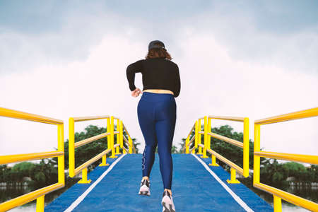 A young woman runs up a hill on a pedestrian bridge over a canal, a blue asphalt road, a yellow guardrail. Female athletes practicing outside