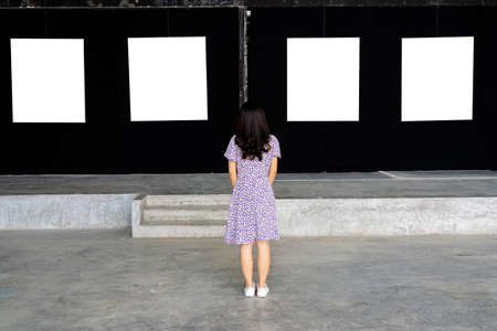 A woman standing and looking at a blank picture frame on a white wall art gallery