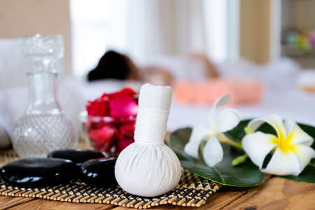 Supplies for massage on bed in modern spa salon. Place for relaxation. Beautiful spa composition on blurred background