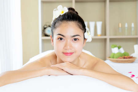 Beautiful young woman in spa salon, enjoying massage in spa