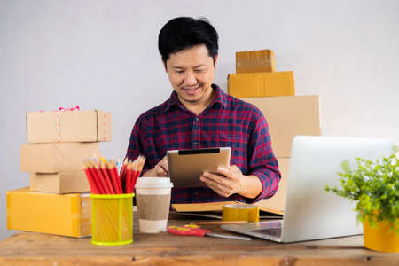 Businessman use tablet thinking with pile of parcel on work desk. Laptop at workplace of start up, small business owner. cardboard parcel box of product for deliver to customer. Online selling concept 版權商用圖片