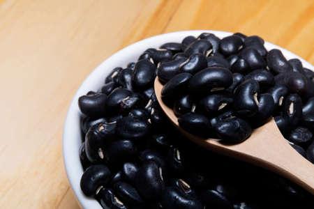 Black gram (Vigna mungo) in wooden spoon with ceramic bowl
