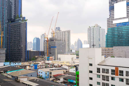 Building under construction at sunset, construction crane is working. Bangkok, Thailand downtown cityscape.