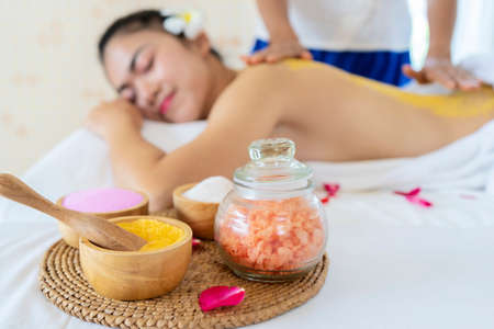 Closeup on spa therapy ingredients and relaxed young woman in background. The young woman is lying and relaxingin. 版權商用圖片