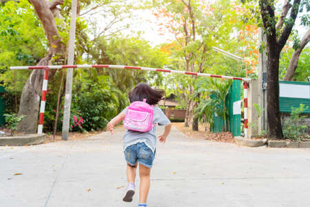 Back to school. Cute asian child girl with backpack running and going to school with fun 版權商用圖片