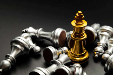 gold queen chess surrounded by a number of fallen silver chess pieces , business strategy concept