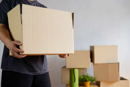 House moving concept. Man holding cardboard box, closeup. Moving boxes in new apartment, real estate 版權商用圖片