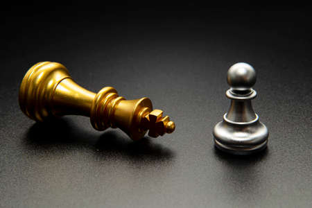 One pawn in front of the king on a black background. The idea of a small person fights the big one and wins. 版權商用圖片