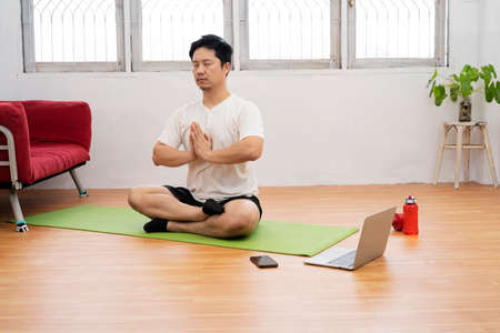 fitness, meditation and healthy lifestyle concept - man meditating in lotus pose at home