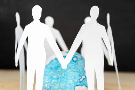 Paper people standing in circle around globe, people connected to each other
