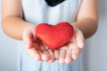 Heart in child hands. Girl giving love to someone. Red heart on cover. Girl made donation to heart. Valentine day of love concept and Healthcare concept.