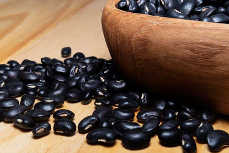 Raw black beans in wooden bowl on table. Black beans has health benefits they are source of protein, filling fiber, disease fighting antioxidants, and numerous vitamins and minerals.