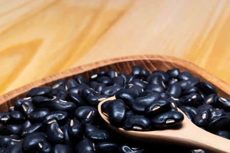 Raw black beans in a wooden spoon and a bowl close up on the table. horizontal view from above