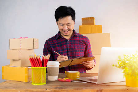 Starting small businesses SME owners man entrepreneurs Write the address on receipt box and check online orders to prepare to pack the boxes, sell to customers, sme business ideas online. 版權商用圖片
