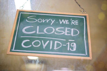Temporarily closed sign for Covid-19 in small business activity. Information notice sign about quarantine measures. Close up on a red closed placard in the window of a shop for coronavirus.