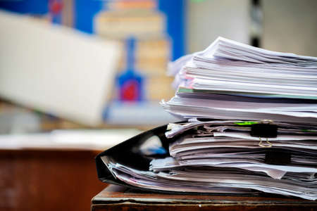 Lots of documents on the desk, tall papers waiting to be dealt with, are placed on the desks.