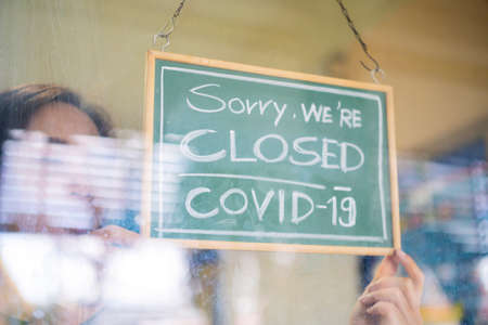 Stressed owner forced to close the restaurant permanently due to restrictions on the coronavirus. Depressed businesswoman closing her business activity due to covid-19. Small business bankrupt.