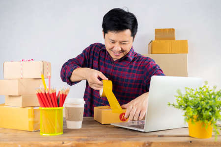 Young startup small business entrepreneur man working with smart phone at home, Online business, ecommerce and delivery concept