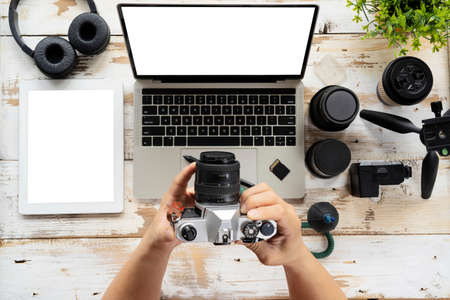 Camera photography design studio editing concept, desktop with photography equipment, camera, tripod,flash and computer. The hand that was holding the camera came to look.