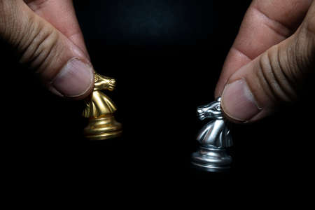 Close-up of a man holding a golden and silver chess horse on a chessboard, copying spaces for your message. Stock Photo