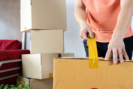 House moving concept. Closeup of man packing cardboard box, moving to a new house Stock Photo