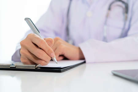 Doctor with a clipboard wrote on paper at the desk in the office. Prescription pills are prescribed by the doctor. Stock Photo