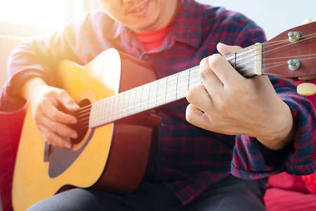 Enjoying carefree time at home. Happy young man playing the guitar while sitting on sofa at home Stock Photo