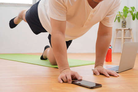 sport, fitness and healthy lifestyle concept - man with tablet computer doing running plank exercise at home Stock Photo