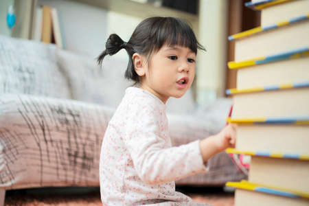 Education and school ideas - Little girl students are studying at school. I am practicing counting from the number of books available.