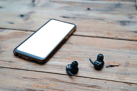 Mobile accessories arrangement band black wireless headphones wireless headphones android mobile top blank wooden background Stock Photo