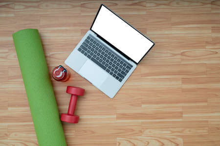 Online home training sports or yoga class concept top view Laptop with yoga mat on the wood floor