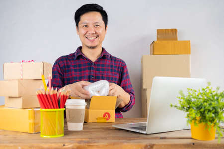 Small business owner packing in the cardbox at workplace. Cropped shot of man preparing a parcel for delivery at online selling business office. Stock Photo
