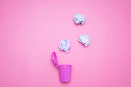 Wrinkled paper is about to fall into pink trash on a pink background. Stock Photo