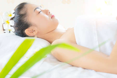 Beautiful young woman relaxes in spa salon