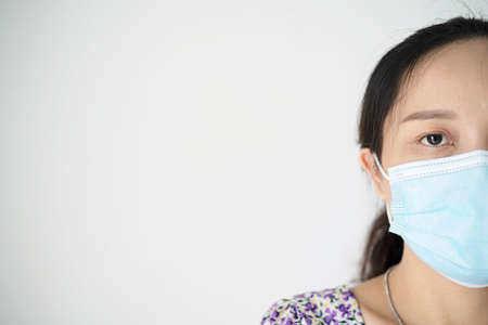 Beautiful young woman wearing protective mask. Studio shot, isolated on white background. Beautiful woman with black hair and brown eyes wearing casual t-shirt standing over white background. Stock Photo