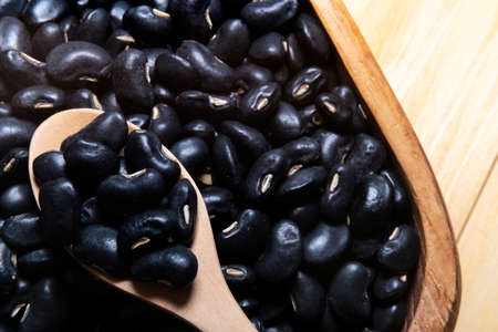 Black beans with a wooden spoon on a bowl are placed on a wooden table.