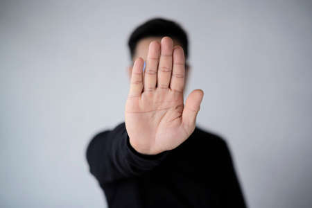 An Asian man with a beard wears a white T-shirt, stretching out his hands and showing the sign to stop. I don't want this. Please stop, as if to reject. In a beautiful cement backdrop