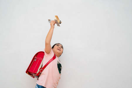 cute girl carrying school bag going to school, happy playing toy plane on gray wall background Freedom to dream