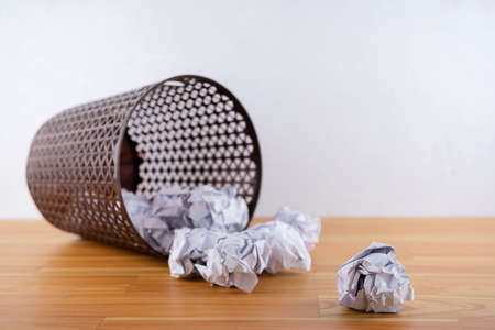 Crumpled paper balls all around a black recycle bin. Placed in the background behind a white wall